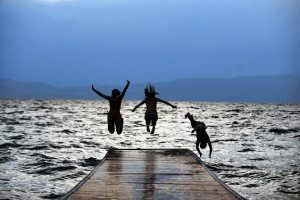Three girls jump in  the Ohrid Lake in O